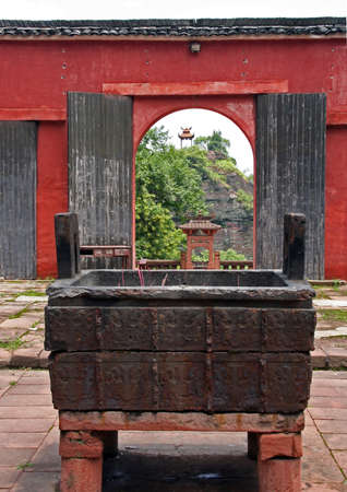 caldron: Qiyun Shan, China  Fragment of a temple courtyard with sacrifice caldron and an open gate in background in Qiyun Mountain, Anhui Provinc