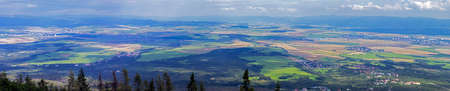 vistas: Large vistas of space down below, meadows, fields, villages and forests seen from top of high mountain   Photo taken in Tatra mountains, Slovak republic  Stock Photo