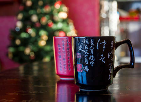 Two mugs red and black decorated with chinese calligraphy, lying on black chinese table likewise decorated with calligraphy signs with blurred christmas tree in background Editorial