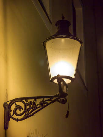 nightscene: Beautiful, decorated lantern attached to the wal of an old house