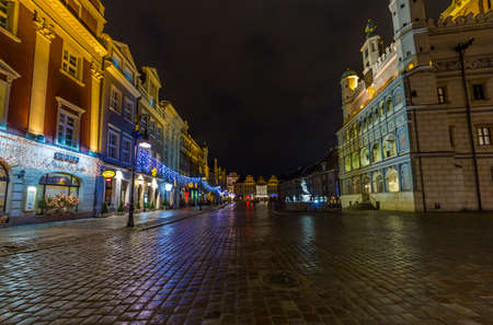 Poznan, Poland - Janurary 10, 2014  Night photo of  historical town square with beautifully decorated townhall on the right and old houses on the left on Janurary 10, 2014