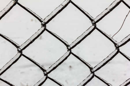 Pattern of chain ling fence with chains covered with ice photo