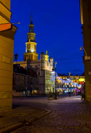 Night photo of an old town square and city hall in Poznan, Poland from one of cobbled, neighbouring streets