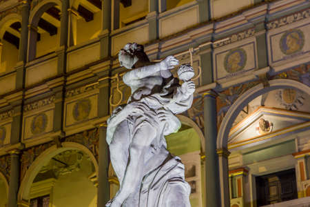 Night photo of historical fountain statue with beautifully decorated facade of the city hall in background, Poznan, Poland photo