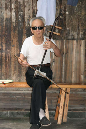 Anhui, China - July 09, 2007  An old man plays the erhu, Anhui, China on July 08,2007  Erhu is one of the most famous traditional chinese musical instruments Redakční