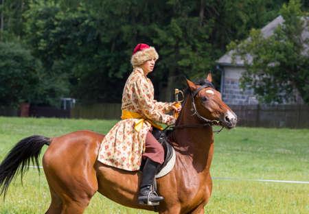 cavalryman: Oblegorek, Polonia - 15 de julio 2012 Historia fan vestido como soldado de caballer�a polaca del siglo 17 con un sable en la mano en un espect�culo de recreaci�n p�blica gratuita en Oblegorek el 15 de julio 2012