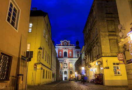 Poznan, Poland - January 10, 2014  Night photo of beautiful cobbled street with Collegiate Church of Our Lady of Perpetual Help and St  Mary Magdalene in the centre on January 10, 2014