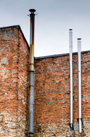 three metal chimneys, one old and rusty and two new and shiny attached to a shabby brick wall of an old building photo