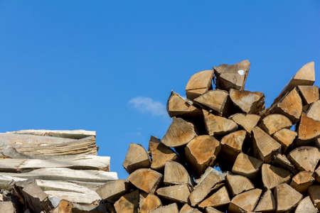 sawmill: Logs of and boards of wood of different shapes, sizes and kinds piled together in saw-mill with blue sky above Stock Photo