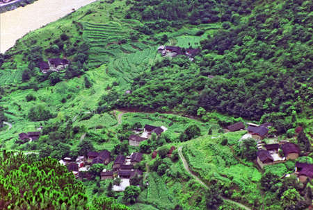 terraced: aerial view of traditional village in china with old cottages and terraced fields, leaping tiger gorge, yunnan,  stylized and filtered to look like an oil painting