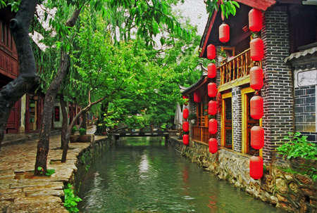 photo of beautiful street in lijiang, china, with a canal; old houses, trees and red lanterns stylized and filtered to look like an oil painting photo