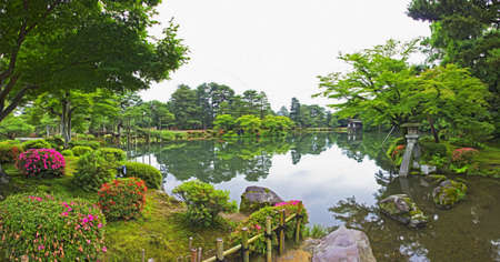 Panoramic photo of a japanese garden with flowers, trees, lake, rocks and stone lantern standing in water, filtered and stylized to resemble an oil painting