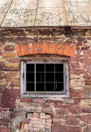Fragment of beaufitul old barn from the beginning of the 20th century with stone wall and a nice brick decor above window frame, vertical photo