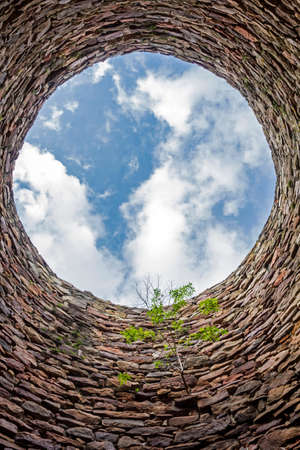 The inside of an old industrial chimney shaft photographed from the bottom - circular stone wall with tree growing from it and blue sky with white clouds in the opening in the centre, vertical photo