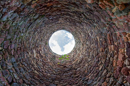 The inside of an old industrial chimney shaft photographed from the bottom - circular stone wall with tree growing from it and blue sky with white clouds in the opening in the centre, horizontal photo