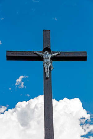 wooden christian cross with Christ figuribe in the background of blue sky and white clouds viewed from below photo