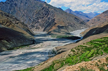 Himalayan valley in Spiti, Himachal Pradesh, India with the river, high mountains and terraced fields, stylized and filtered to look like an oil painting photo