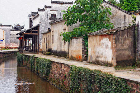 the canal of an ancient village in Anhui province, china, stylized and filtered to resemble an oil painting  photo