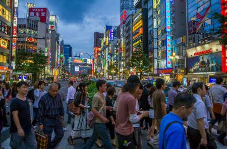 Tokio, Japón - 26 de junio 2010 Una multitud de personas en un cruce ocupado en el distrito de Shinjuku por la noche con las luces de neón en el fondo el 26 de junio de 2010 en Tokio, Japón Editorial
