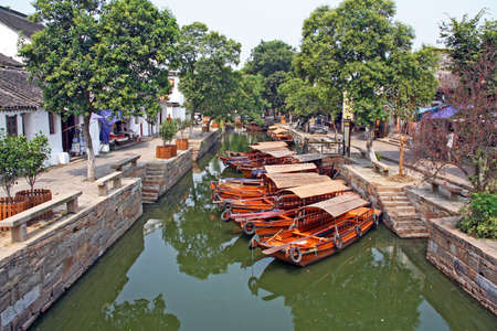 zhouzhuang: Photo of a canal in ancient Tongli watertown near Suzhou, China with traditional boats and old houses on both sides Editorial