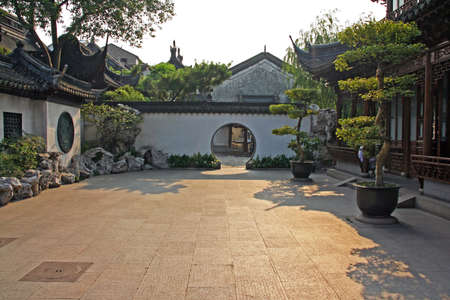 courtyard: Photo of a fragment of  Yuyuan gardens, Shanghai wth courtyard, bonsai trees and moon gates