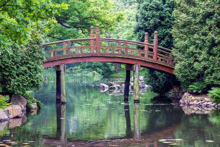 japanese red bridge - taiko bashi, characteristic element of japanese gardens photo