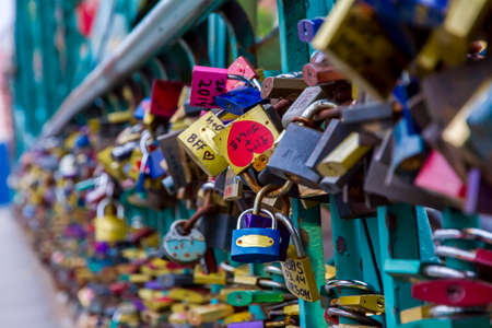 declare: Many colorful padlocks locked together on a bridge in Wroclaw in order to bring good fortune or declare love  Only middle padlocks in focus  Editorial