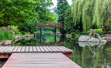japanese bridge: Pier in japanese garden with red japanese bridge in background