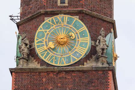 Fragment of the main tower of the city hall, Wroclaw, Poland with an old clock in the centre and beautiful statues on both sides photo