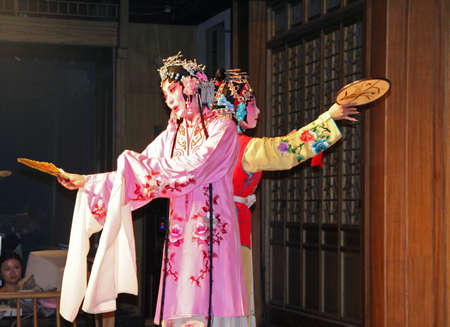 Suzhou, China - July 22, 2007  Two female actors in traditional costumes with faces under thick layer of make-up perform chinese opera at a show for tourists in one of the gardens in Suzhou on July 22, 2007