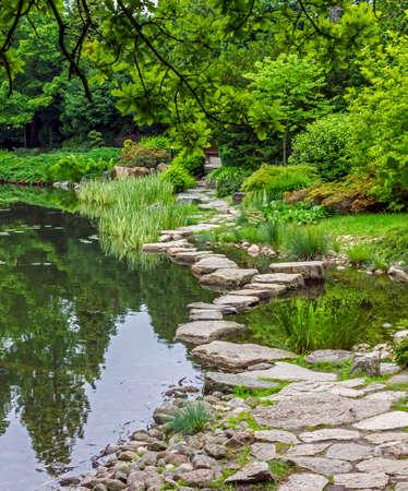 vlonder: Loopbrug over de vijver gemaakt van stenen Dit element van de Japanse tuin is Ishibashi genoemd Stockfoto