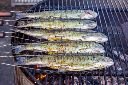 five trout fish grilled on a barbeque in an open door restaurant photo