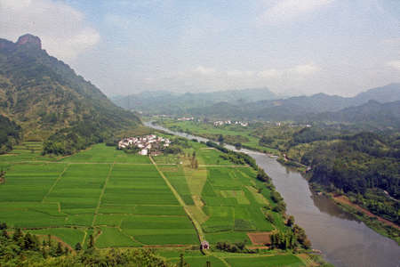 anhui: panorama of beautiful chinese contryside with river, fields, mountains and village, Anhui Province, stylized and filtered to look like an oil painting Stock Photo
