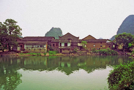 anhui: photo of generic  chinese landscape stylized and filtered to look like an oil painting. In foreground river, in background ancient village. Location - Yanhsguo.