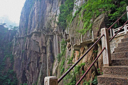 huang: The pathway made on the vertical slope of a mountain, Huang Shan (Yellow Mountains), China, stylized and filtered to look like an oil painting.