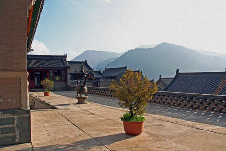 stupa: Buddhist Nanshan temple in Wutaishan, China stylized and filtered to look like an oil painting.. In the foreground courtyard and temple buildings, in the background mountains lit by the setting sun