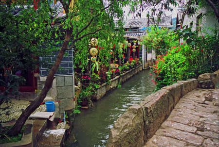 chinese courtyard: photo of beautiful street in lijiang, china, with a canal; old houses, trees and red lanterns stylized and filtered to look like an oil painting Stock Photo