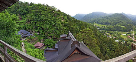 buddhist temple roof: Yamadera, Japan - June 28, 2010: Panoramic photo of the roofs of the famous Yamadera buddhist temple complex in Tohoku with beautiful rural countryside and mountains in background on June 28, 2010. Editorial