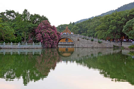 anhui: generic  chinese garden architecture, stylized and filtered to look like an oil painting. In foreground a pond, in background chinese bridge Stock Photo