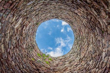 tunel: The inside of an old industrial chimmey shaft photographed from the bottom - circular stone wall with tree growing from it and blue sky with white clouds in the opening in the centre, horizontal