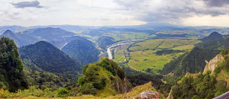 windings: Panoramic photo of Pieniny Mountains, Poland with large vistas of space down below:  peaks, forest, meadows, fields and villages.