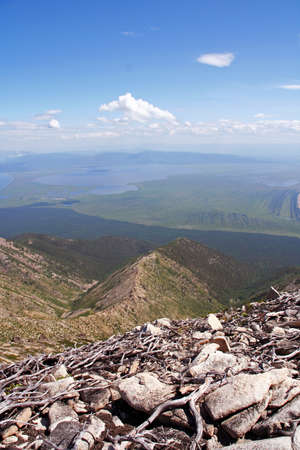 vast: Vast view from the top of a mountain at the shores of Lake Baikal, Russian Siberia with stones and twigs in foreground, and mountains and lake in background Stock Photo