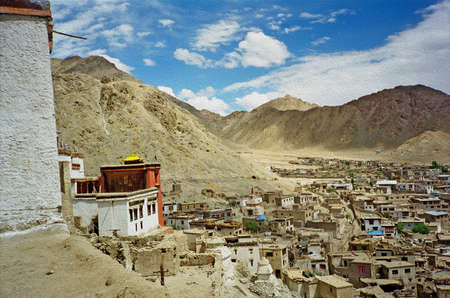 indian village: Leh, the capital of Ladakh seen from the hilll with Leh gompa in foreground and mountains in background,  stylized and filtered to resemble an oil painting oil paint stylization Stock Photo