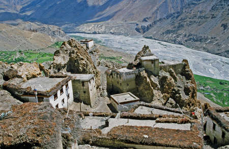 indian village: Traditional Himalayan flat roof houses in Dhankar village  with a spectacular gorge and river valley in background in Spiti valley, Himachal Pradesh,  stylized and filtered to resemble an oil painting Stock Photo