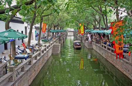 filtered: A canal in ancient Tongli watertown near Suzhou with traditional boats and old houses on both sides, Jiangsu province,  stylized and filtered to resemble an oil painting
