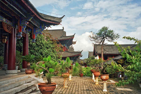 chinese courtyard: vintage style photo of courtyard of palace in lijiang, china with beautiful artificially shaped plants and trees
