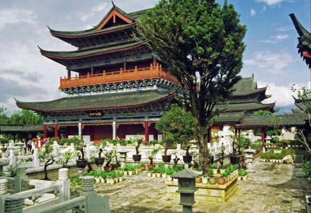 artificially: vintage style photo of fragments of ancient mu palace in lijiang, china with richly decorated large halls and beautiful courtyards and bridges