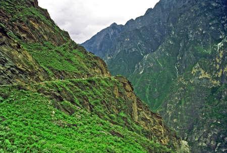 背景の霧にむせぶ山中虎渓谷、雲南省、中国の跳躍の山の側につながるパスのビンテージ スタイル写真