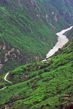 タイガー渓谷、雲南省、中国の跳躍の垂直のビンテージ スタイル写真-山側と霧にむせぶ峡谷の川村