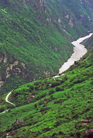 vertical vintage style photo of  leaping tiger gorge, yunnan, china -village on mountain side and river winding in the canyon enshrouded with mist